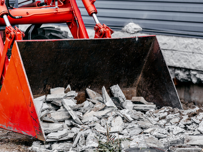 Concrete being picked up by a Kubota after a concrete tear out